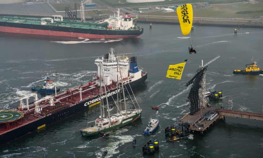 Greenpeace Rainbow Warrior, paragliders and Greenpeace inflatables surrounding Russian oil tanker Mikhail Ulyanov to protest against first shipment of arctic oil in Rotterdam.