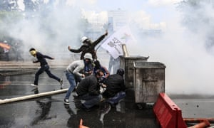Turkish protesters take cover as riot police fire tear gas to disperse a rally near Taksim square.