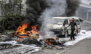 A masked Turkish protester stands next to burning tyres during clashes at a May Day rally near Taksim square in Istanbul.