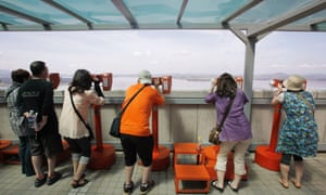 Japanese tourists in South Korea look at a village in North Korea's Kaepoong county through binoculars.