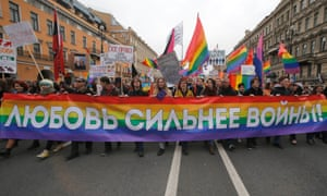 """Gay rights activists march during a May Day rally in St Petersburg, Russia. The banner reads, """"Love is stronger than war!"""""""