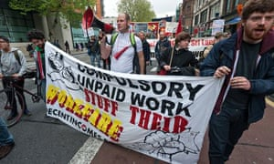 Demonstrators march in London with a  workers' rights banner on May Day