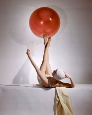 Reclining model in white swimsuit and bathing cap, balancing large red ball on feet Fashion