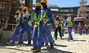 Migrant workers leave a construction site in Doha, Qatar