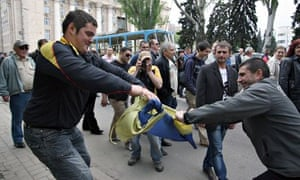 Pro-Russian protesters try to destroy a Ukraine fl