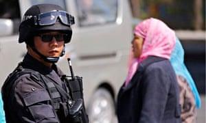 A paramilitary policeman guards the Urumqi South railway station,