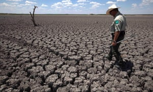 Texas State Park police officer Thomas Bigham walks across the cracked lake bed of O.C. Fisher Lake in San Angelo, Texas.  A new study suggests we're in for a hot future unless we act to curb greenhouse gas emissions.