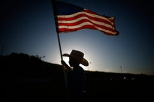 From the agencies: Esteban Edwards holds a US flag at the rodeo in Truth or Consequences