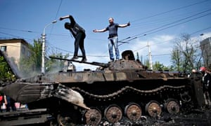 People stand on top of burnt-out armoured personal carrier near the city hall in Mariupol on the eve