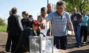 A local resident casts his ballot into a portable ballot box in the village of Ternovoe outside Luhansk.