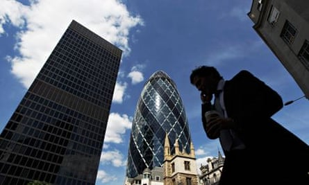 A man passes the Swiss RE building (known as the Gherkin) in the City of London