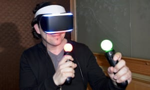 A man wears the Morpheus headset, which consists of screens in front of the eyes held on by a white headband
