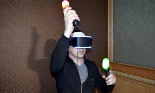 A VR headset-wearer moves his hands around, holding the controllers which have coloured lights on them