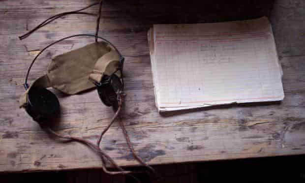 Listening devices (a pair of headphones) and an old notebook on a desk at Bletchley