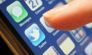 Someone's index finger hovers over the Twitter app button on a smartphone