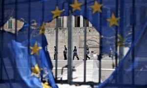 Police seen through a burned EU flag at the Greek parliament in Athens on 1 May 2013
