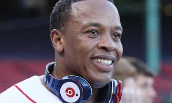 Dr Dre smiles broadly with a pair of Beats headphones round his neck