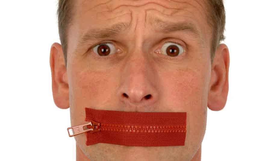 Close-up of man looking quizzical with red zip plastered across his mouth