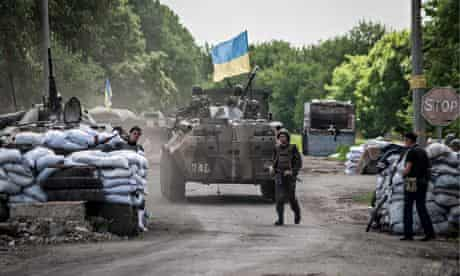 Ukrainian soldiers stand guard at a checkpoint
