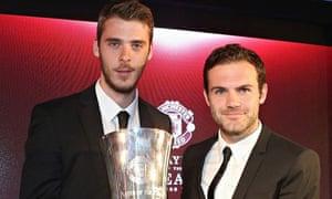 Manchester United's David de Gea is presented with an award by Juan Mata.