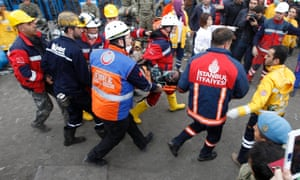 Rescuers carry a miner who sustained injuries after a mine explosion, to an ambulance in Soma, a district in Turkey's western province of Manisa
