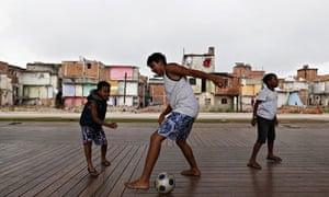 Children play football in the Manguinhos slums in Rio de Janeiro