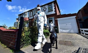A forensic officer with a dog outside the house in North Shields.