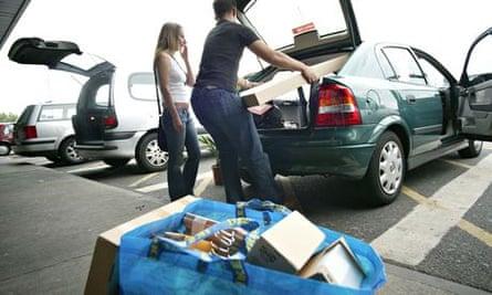 a couple loading IKEA furniture into car