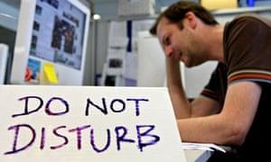 A man with a Do Not Disturb sign