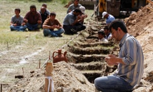 A man prays beside a grave of a dead miner while workers dig graves and locals accompany the praying in a cemetery in Soma