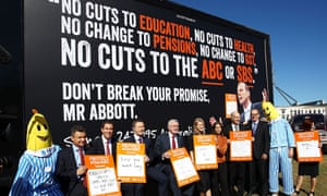 Ministers and senators pose for media in front of a billboard showing an image of Prime Minister Tony Abbott at a ABC protest rally.