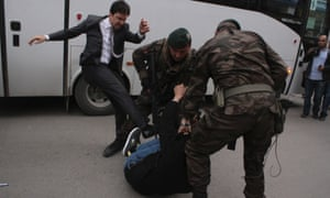 A protester is kicked by Yusuf Yerkel, an adviser to Turkey's Prime Minister Tayyip Erdogan, as Special Forces police officers detain him during a protest against Erdogan's visit to Soma,