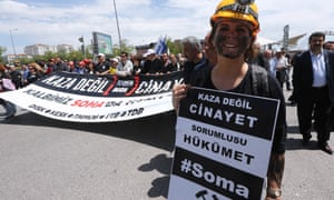 "A woman with a blackened face and a miner's helmet holds a sign reading ""This is not an accident, this a murder. The government is responsable."" as she and other take part in a protest against the government of Turkish Prime Minister Recep Tayyip Erdogan, in Ankara, three days after an explosion and fire at a coal mine in Soma in western Turkey which killed hundreds of workers."