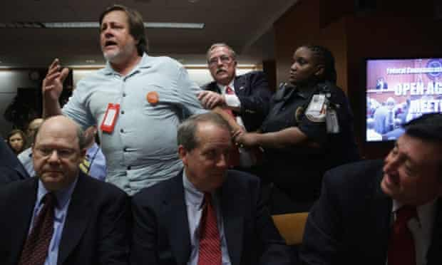 Activist Kevin Zeese is pulled away as he protests during an open meeting on internet regulation.  net neutrality