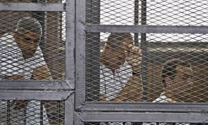 Al-Jazeera journalists Mohammed Fahmy, Peter Greste and Baher Mohamed in a cage inside a Cairo court