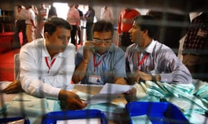 Election officials count the postal ballots at a counting centre for India's parliamentary elections in New Delhi.