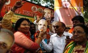 Supporters of the Bharatiya Janata Party (BJP) hold up a mask of opposition candidate Narendra Modi, as they celebrate after learning of initial poll results outside their party office in Mumbai.