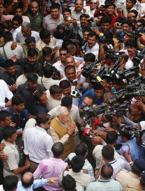 BJP eader and India's likely next prime minister Narendra Modi greets the media as he leaves his 90-year-old mother's house in Gandhinagar, in the western Indian state of Gujarat.