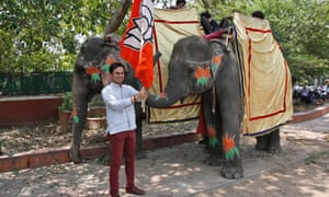 A supporter of the Bharatiya Janata Party holds the party flag and stands next to elephants decorated with the party symbol outside the party headquarters in New Delhi, India.