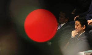 Japan's Prime Minister Shinzo Abe attends parliament in Tokyo.The red spot is from a TV camera's lamp.
