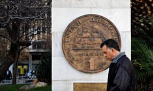 A pedestrian passes a sculpture of the Greek one drachma coin in Athens, Greece