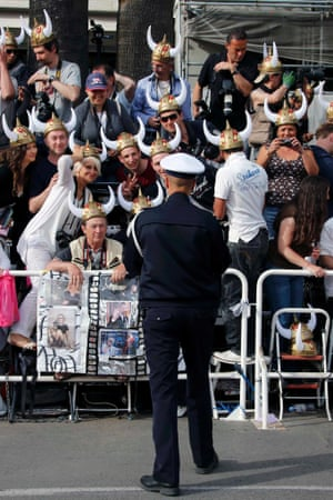 """A French Police officer takes a picture of cinema fans wearing Viking helmets as they wait for arrivals in front of the Festival Palace before the screening of the film """"How to Train Your Dragon 2""""."""