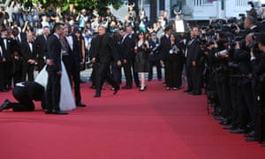 An unidentified man runs onto the red carpet and crawls under the skirt of actress America Ferrera