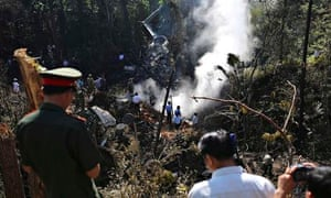 Rescue workers search an air force plane crash site in Xiang Khouang province, Laos
