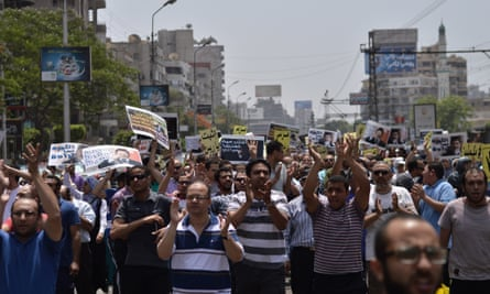 Protesters tear up Abdel Fattah El-Sisi presidential banners.
