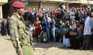 Police officer stand guard as people gather at the site of twin explosion at Gikomba market. kenya nairobi