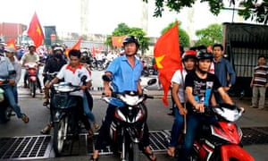 Protesters carry Vietnamese national flags in Binh Duong province