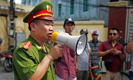 Policemen disperse protesters near China's embassy in Hanoi on Sunday.