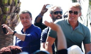 Sylvester Stallone,  Mel Gibson and Dolph Lundgren pose on a tank as they arrive on the Croisette to promote the film The Expendables 3