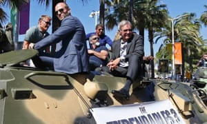 Dolph Lundgren, Jason Statham, Mel Gibson, Sylvester Stallone and Harrison Ford pose on a tank as they arrive on the Croisette to promote the film The Expendables 3.